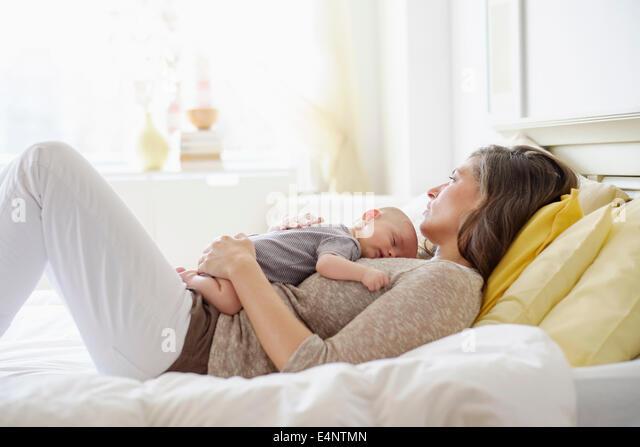 Mutter mit Baby Boy (2-5 Monate) im Bett liegen Stockbild
