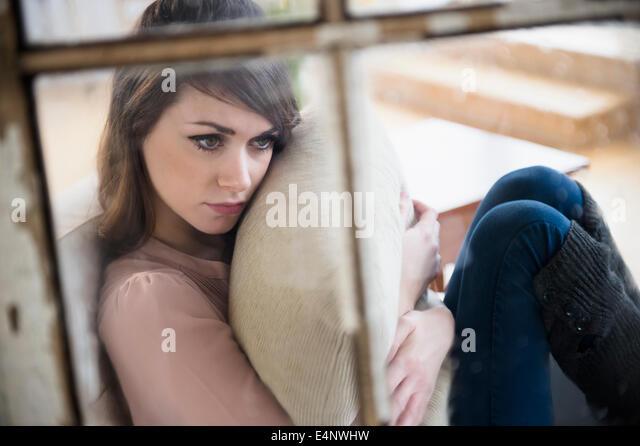 Junge Frau im Wohnzimmer mit Kissen in Händen Betrachtung Stockbild