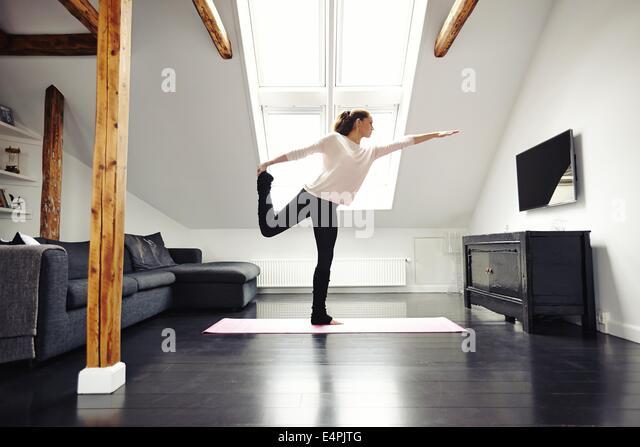 Fitness Frauen Gymnastik im Wohnzimmer. Stretching und balancieren auf einem Bein zu Hause. Kaukasischen Frauen Stockbild