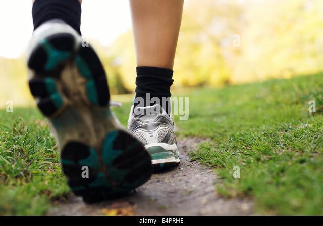 Füße eines Läufers im Park. Frau zu Fuß in den Park, Nahaufnahme der Füße. Fitness Stockbild