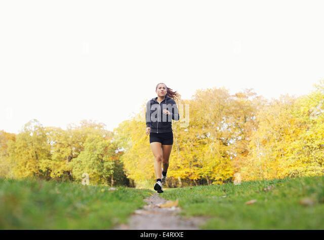 Fit und gesund junge Frau läuft draußen im Park. Fitness-Modell in Sportbekleidung Joggen im Freien. Gesundheit Stockbild