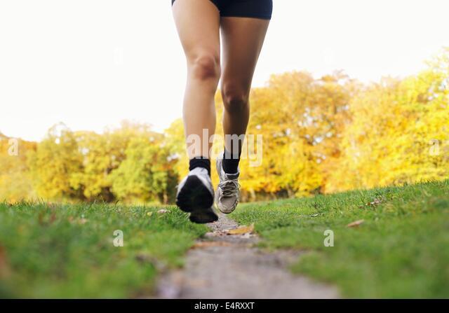 Nahaufnahme der Füße eines Läufers im Park laufen. Frau für Fitness training. Weibliche Beine Stockbild