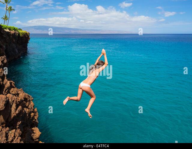 Frau von Klippe ins Meer zu springen. Sommerspaß Lebensstil. Stockbild