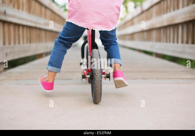 Ein Kind reitet auf einem Fahrrad auf einem Holzsteg. Stockbild