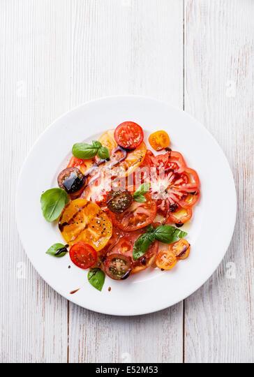 Reife frische bunte Tomaten Salat mit Olivenöl und Balsamico-Essig auf weißem Holz Hintergrund Stockbild