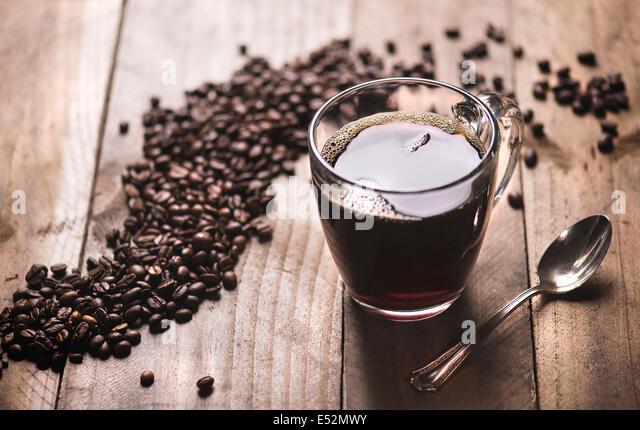 Kaffee in Klarglas mit Kaffeebohnen auf rustikale Oberfläche des Holzes. Stockbild