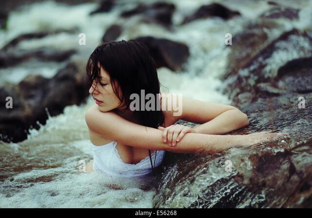 Junge Frau sitzt in einem Bach Stockbild