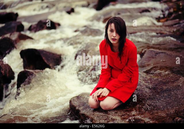 Junge Frau sitzt an einem Bach Stockbild