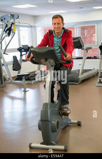 Mann am Heimtrainer in einem Fitnessstudio trainieren Stockbild