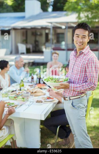 Mann mit Freunden am Tisch im freien Stockbild