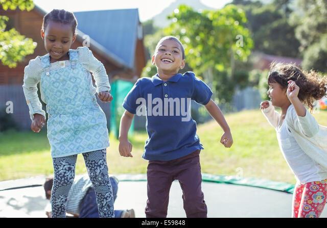 Kinder springen auf dem Trampolin im freien Stockbild