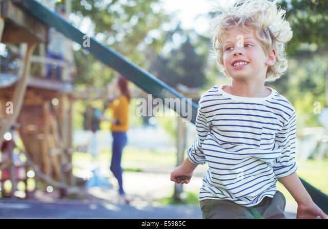 Junge spielt auf Spielplatz Stockbild