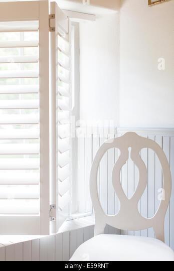 Stuhl von Fenster mit Holzjalousien Stockbild