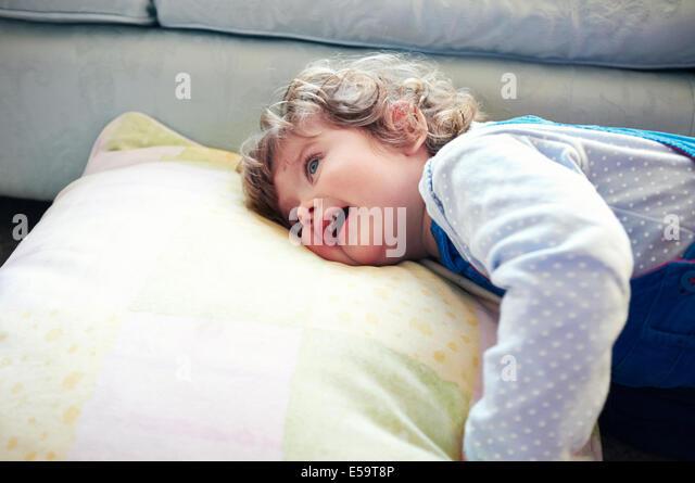 Mädchen auf Kissen im Wohnzimmer verlegen Stockbild
