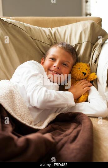 Ruht auf dem Bett mit Teddy Boy Stockbild