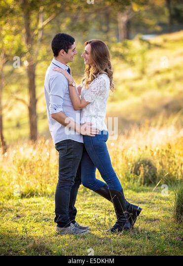 junges Paar in Umarmung in einer ländlichen Umgebung stehen Stockbild