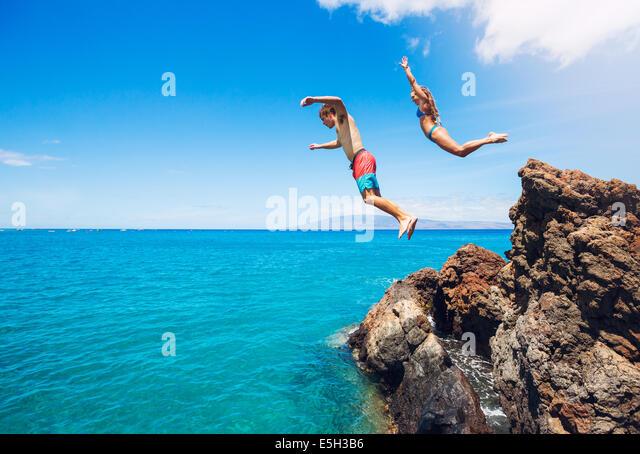 Freunde-Klippen springen ins Meer, Sommerspaß Lebensstil. Stockbild