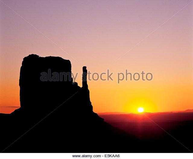 Sonnenaufgang hinter dem West Mitten Butte im Monument Valley, einem Navajo Tribal Park im Navajo Reservat in Arizona Stockbild