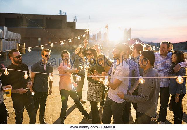 Party-Freunde mit Wunderkerzen urbanen Dachterrasse genießen Stockbild