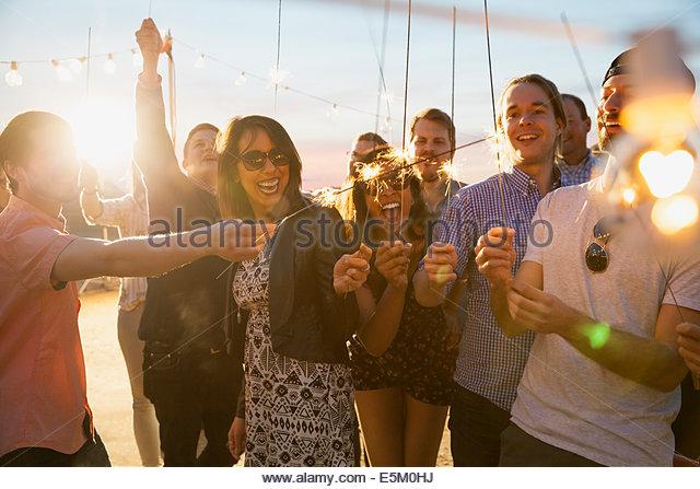 Freunde mit Wunderkerzen, die Partei zu genießen Stockbild