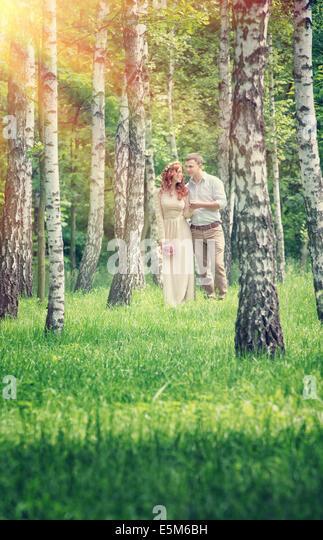 Liebespaar zwischen Birken im Park im sonnigen Tag zu laufen, halten Sie Hände, glücklich Hochzeitstag, Stockbild