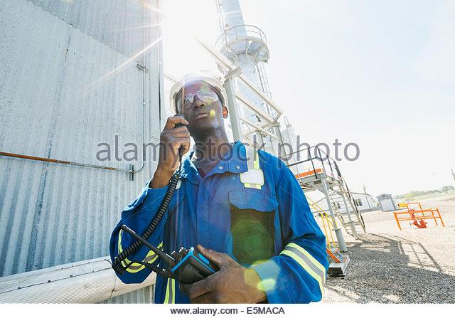 Männliche Arbeiter mit Walkie-talkie bei Gasanlage Stockbild