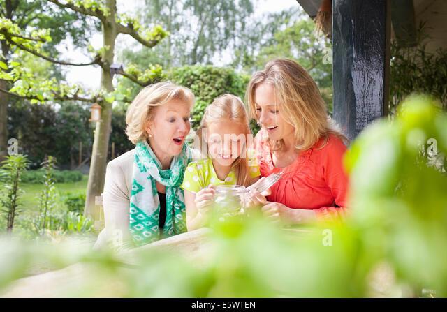 Mädchen Eröffnung Glas von Münzen mit Familie Stockbild