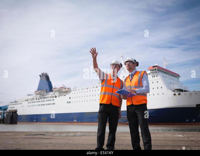 Hafenarbeiter mit Schiff im Hafen Stockbild