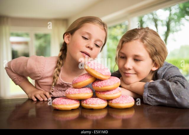 Zwei Schwestern Blick auf Stapel mit Donut Löcher auf Küchentisch Stockbild