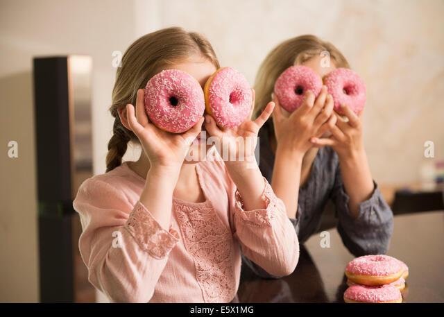 Porträt von zwei Schwestern mit Donut Löcher über den Augen Stockbild