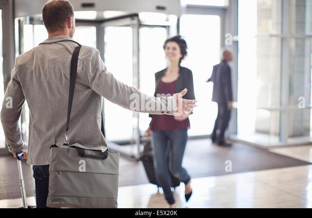 Junger Geschäftsmann Waffen für Freundin im Konferenz-Center Atrium öffnen Stockbild