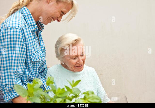 Ältere Frau und Enkelin im Chat am Gartentisch Stockbild