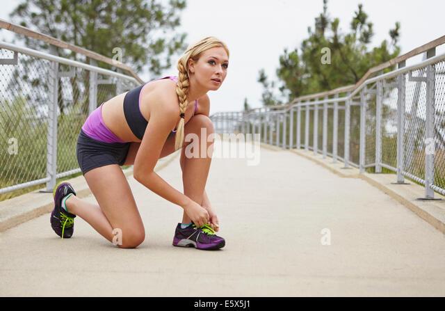 Frau, die Schnürsenkel zu binden, auf Brücke Stockbild