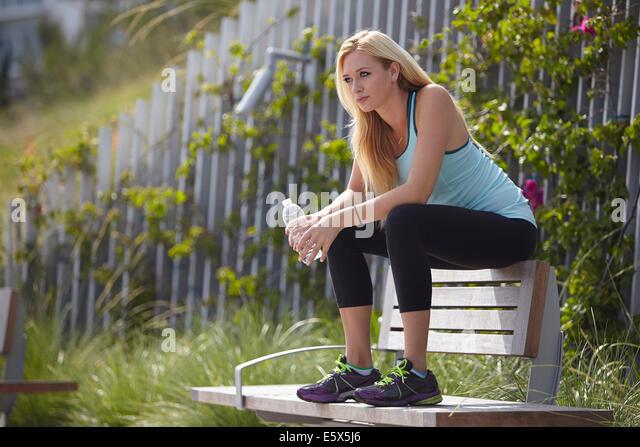Frau sitzt auf der Parkbank Stockbild