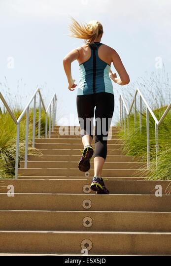 Frau rennt die Treppe hinauf Stockbild