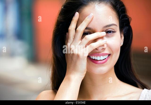 Porträt der jungen Frau mit der Hand bedeckte Gesicht Stockbild