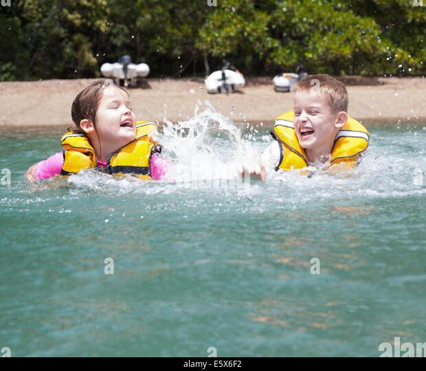 Bruder und Schwester zu spielen, kämpfen und planschen im Meer Stockbild