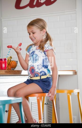 Mädchen sitzen auf Küchenhocker mit Himbeeren an den Fingern Stockbild