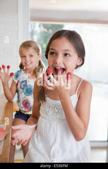 Zwei Schwestern mit Himbeeren an ihren Fingern in Küche Stockbild