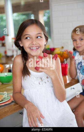 Zwei schelmische Schwestern mit Himbeeren an ihren Fingern in Küche Stockbild