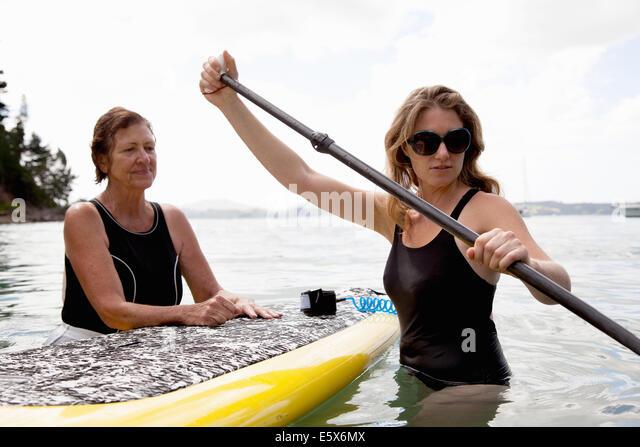 Ältere Frau und Tochter waten mit Paddleboard auf hoher See Stockbild