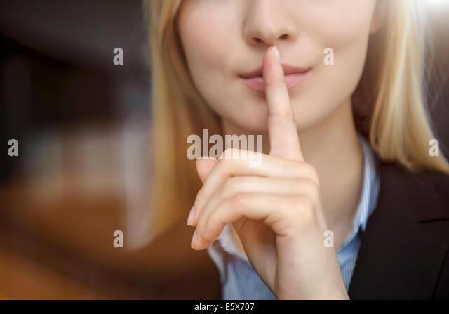 Zugeschnittenes Bild der jungen Unternehmerin mit Finger auf Lippen hautnah Stockbild