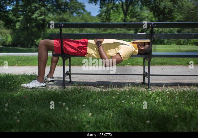 Seitenansicht der junge Mann auf der Parkbank liegend mit Fedora für Gesicht Stockbild