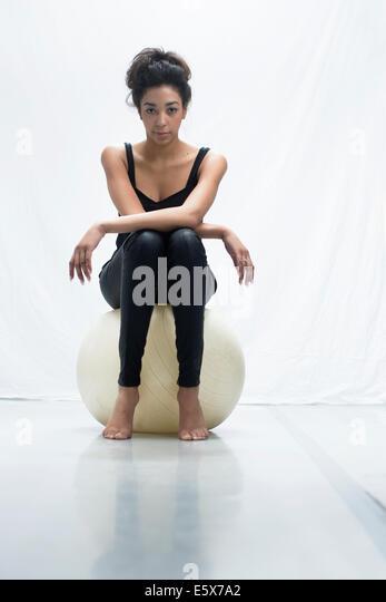 Studio-Porträt der selbstbewusste junge Frau sitzen auf Gymnastikball Stockbild