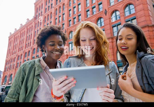 Drei junge Frauen Blick auf digital-Tablette in der Straße Stockbild