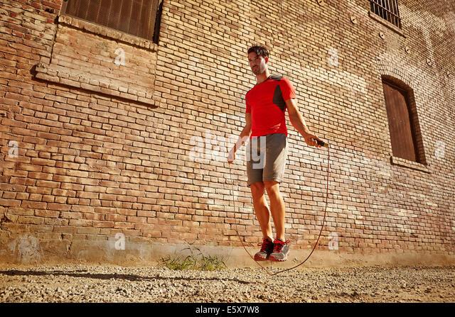 Junger Mann mit Seilspringen auf einer Brache Ausübung Stockbild