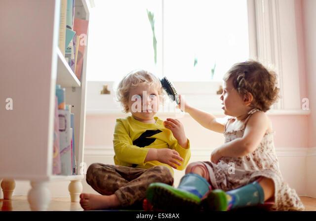 Weiblichen Kleinkind Bürsten männlichen Kleinkindern Haare im Spielzimmer Stockbild