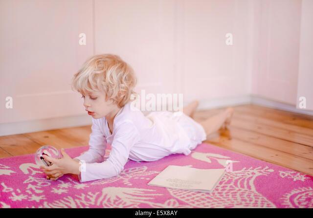 Vier Jahre alter Junge auf Teppich anzustarren Schneekugel liegend Stockbild
