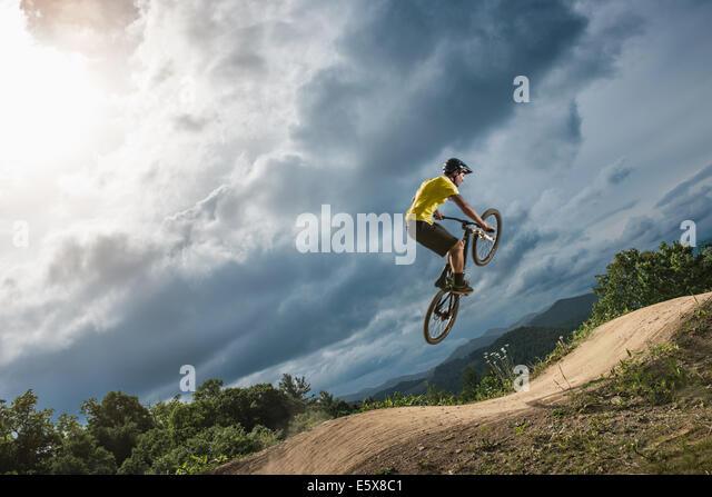 Junge männliche Mountainbiker springen Luft auf ländlichen Pumptrack Stockbild