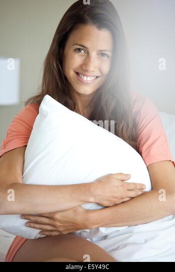 Frau umarmt Kissen zur Selbsthilfe, Porträt Stockbild